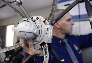 AP PHOTO/THE LANSING STATE JOURNAL|ROD SANFORD Lieutenant Chris Bush of the Michigan State Police shows off the state's first authorized drone before a demonstration in Lansing on March 11. The FAA recently gave the state police the authorization to use drones for crime scene accidents and search and rescue investigations.