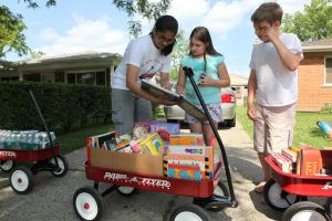 A Red Wagon volunteer skims through a book with two children recipients.