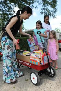"""A Red Wagon volunteer helps a child choose a book to read from the """"library on wheels."""" Photos courtesy of Schoolcraft College."""
