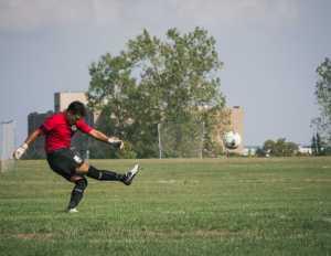 Schoolcraft Freshman Goalkeeper Jose Jimenez, (#13), takes a goal kick to start the Ocelots push for another goal on Sunday.