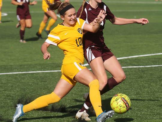 Two soccer players from opposing teams vying over possession of the ball.