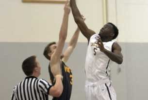 Schoolcraft's Tariq Jones goes in for a tip off against Mott Community College player, Sean Corcoran.