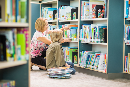 Teacher-librarian assisting boy in selecting books from bookshelf in library