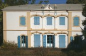 Cette grande bâtisse en pierre et en brique, achevée en 1788, s'inspire d'un modèle d'architecture de Pondichéry. Ce comptoir français, situé au sud-est de l'Inde, entretient au XVIIIème siècle d'étroites relations commerciales avec l'île Bourbon. Après la destruction du comptoir par les anglais en 1761, les maisons y sont reconstruites en s'inspirant du goût néoclassique alors à la mode en France.  Construite sur deux niveaux, la maison Panon-Desbassayns se caractérise par un plan rectangulaire dit «plan massé», une toiture-terrasse en argamasse pour le séchage du café, une distribution symétrique des éléments de la façade et des pièces intérieures, la présence d'un fronton sur la façade Est et de deux varangues à lourdes colonnes sur la façade Ouest.