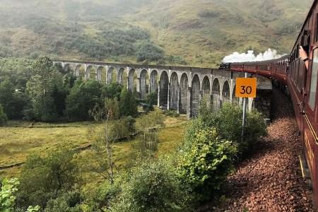 Waehrend der Bahnreise durch Schottland faehrt der Jacobite Train ueber das Glenfinnan Viaduct.