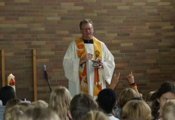 Pfarrer Wellenbrock spendet den Segen für das neue Schuljahr mit Weihwasser.