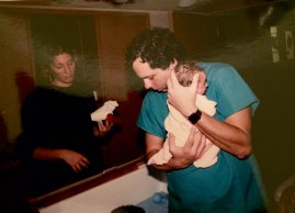 Dad holding me as a newborn