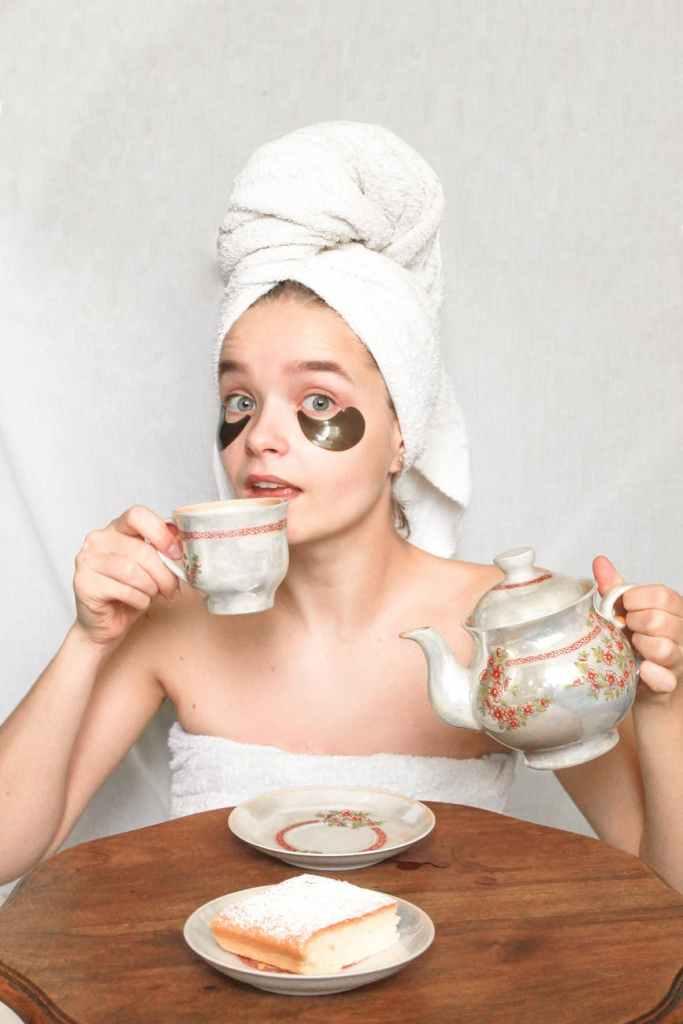 woman in washcloth drinking tea