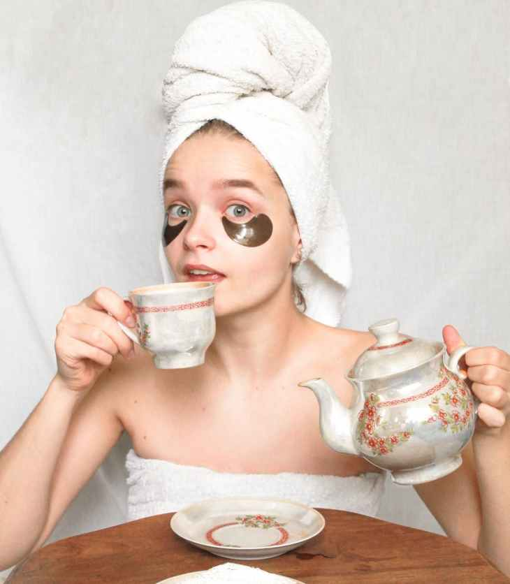 woman in washcloth drinking tea
