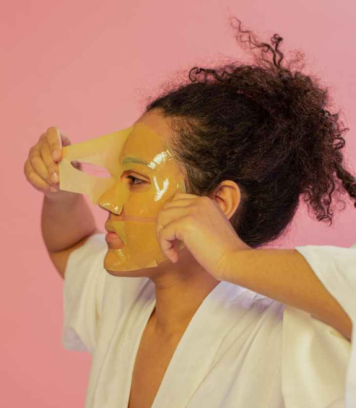 black woman removing hydrogel mask from face