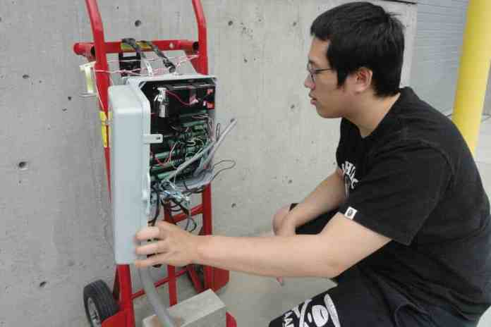 Chemical engineering student Ka Fung Wong inspects sensors that are buried under the concrete test plot.