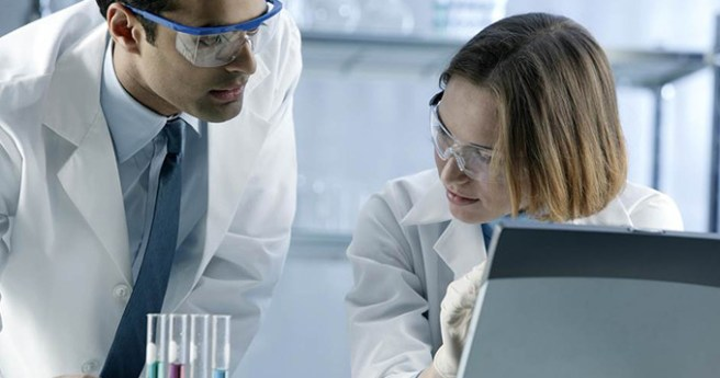 Investigator scientists in a lab discussing results at a computer
