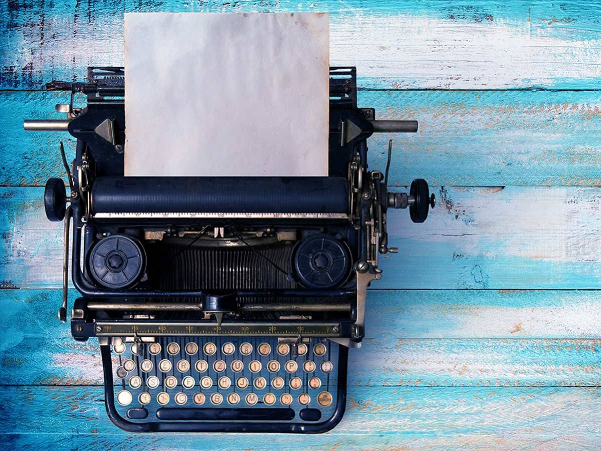 Vintage typewriter header with old paper retro machine technology - top view and creative flat lay design