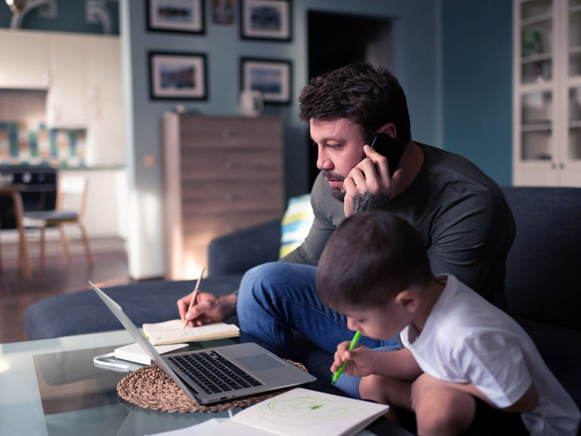 Man working near drawing son at home