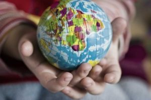 Child's hands holding a globe