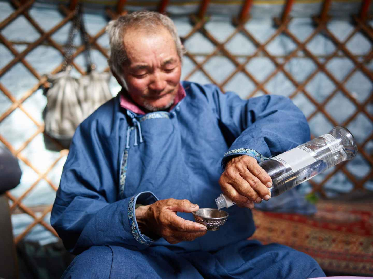 ethnic man pouring vodka in singing bowl