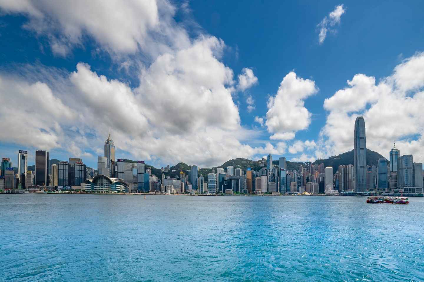city buildings near body of water under blue sky and white clouds