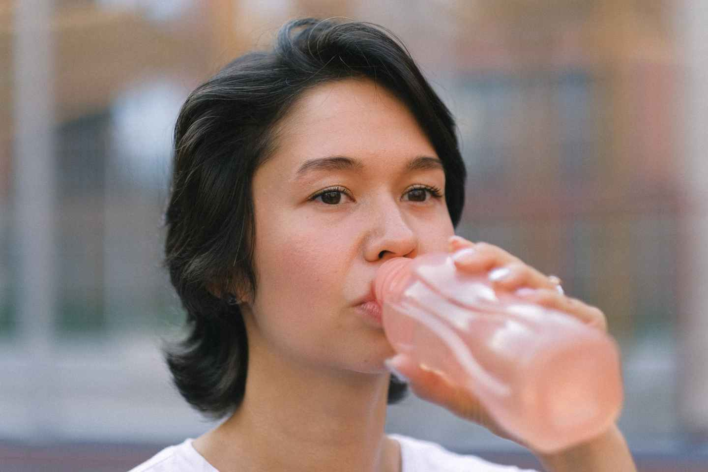 female drinking water on sports ground