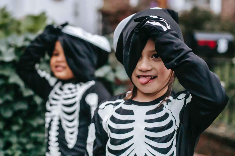 multiracial kids in halloween costumes in neighborhood