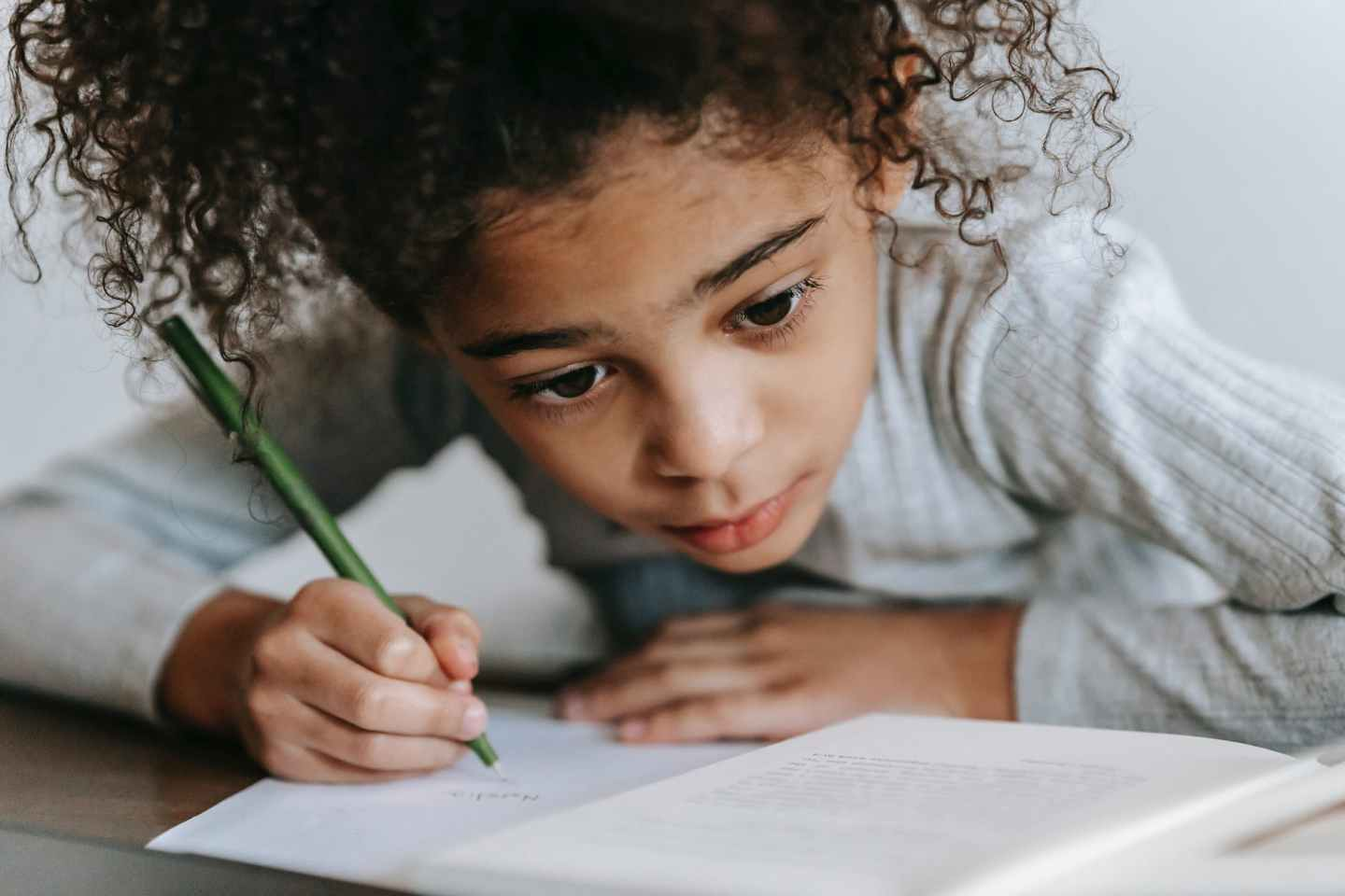 focused black girl writing on paper