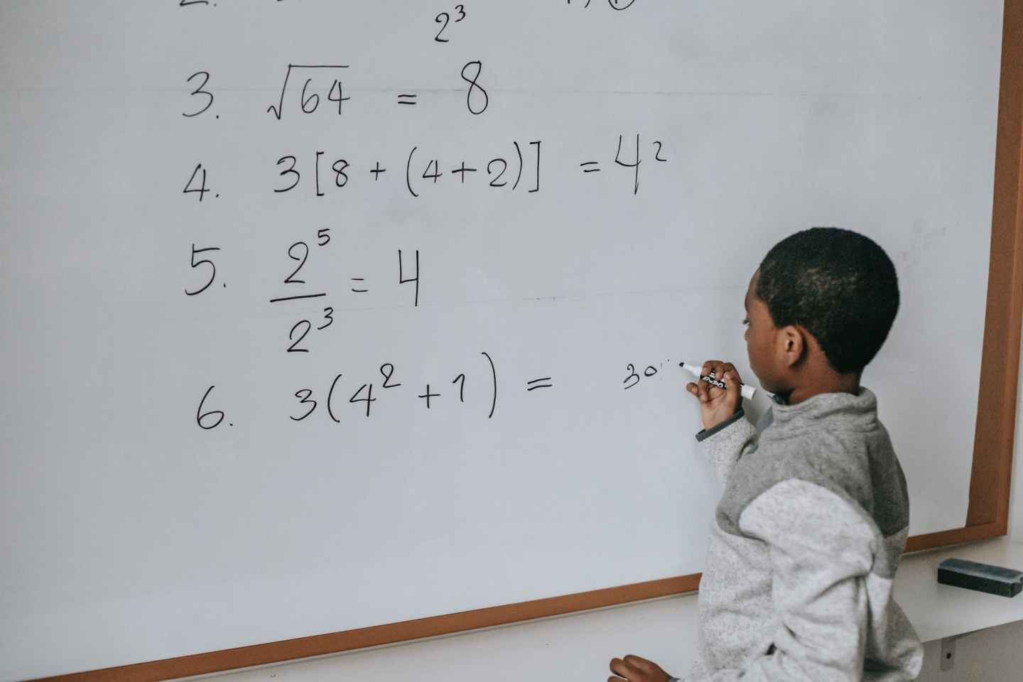 black schoolboy solving math examples on whiteboard in classroom