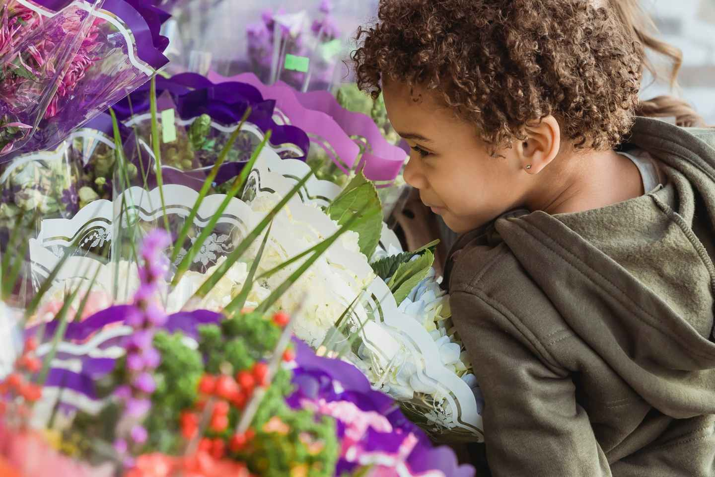 crop cute black boy smelling aromatic flowers in floral store