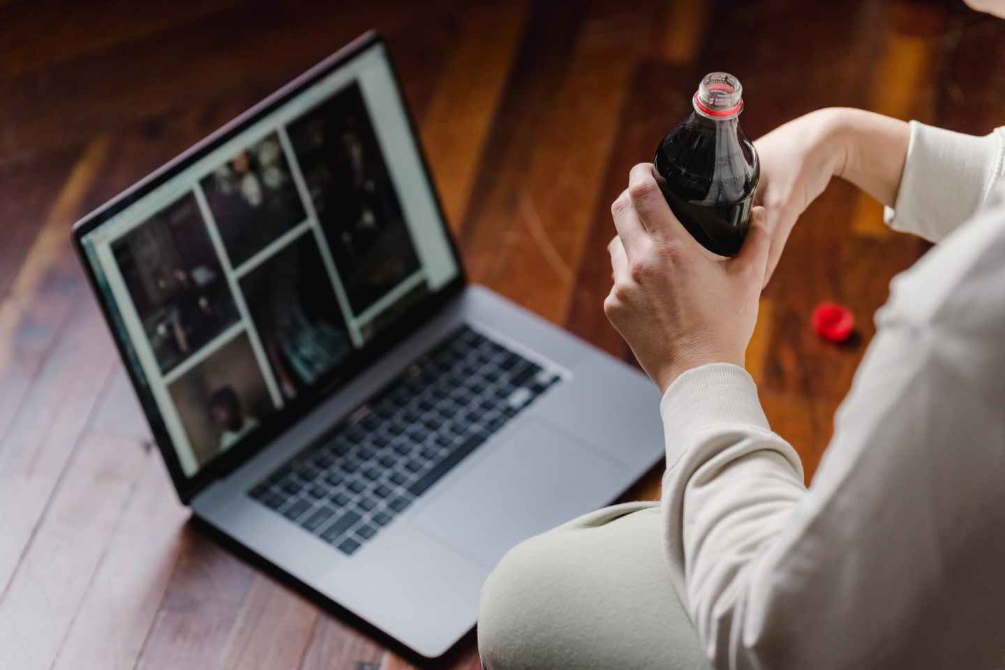 crop person with soda sitting on floor with laptop