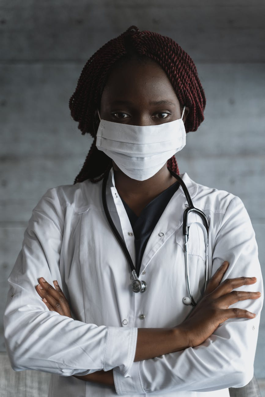 photo of woman with stethoscope hanging on the back of her neck