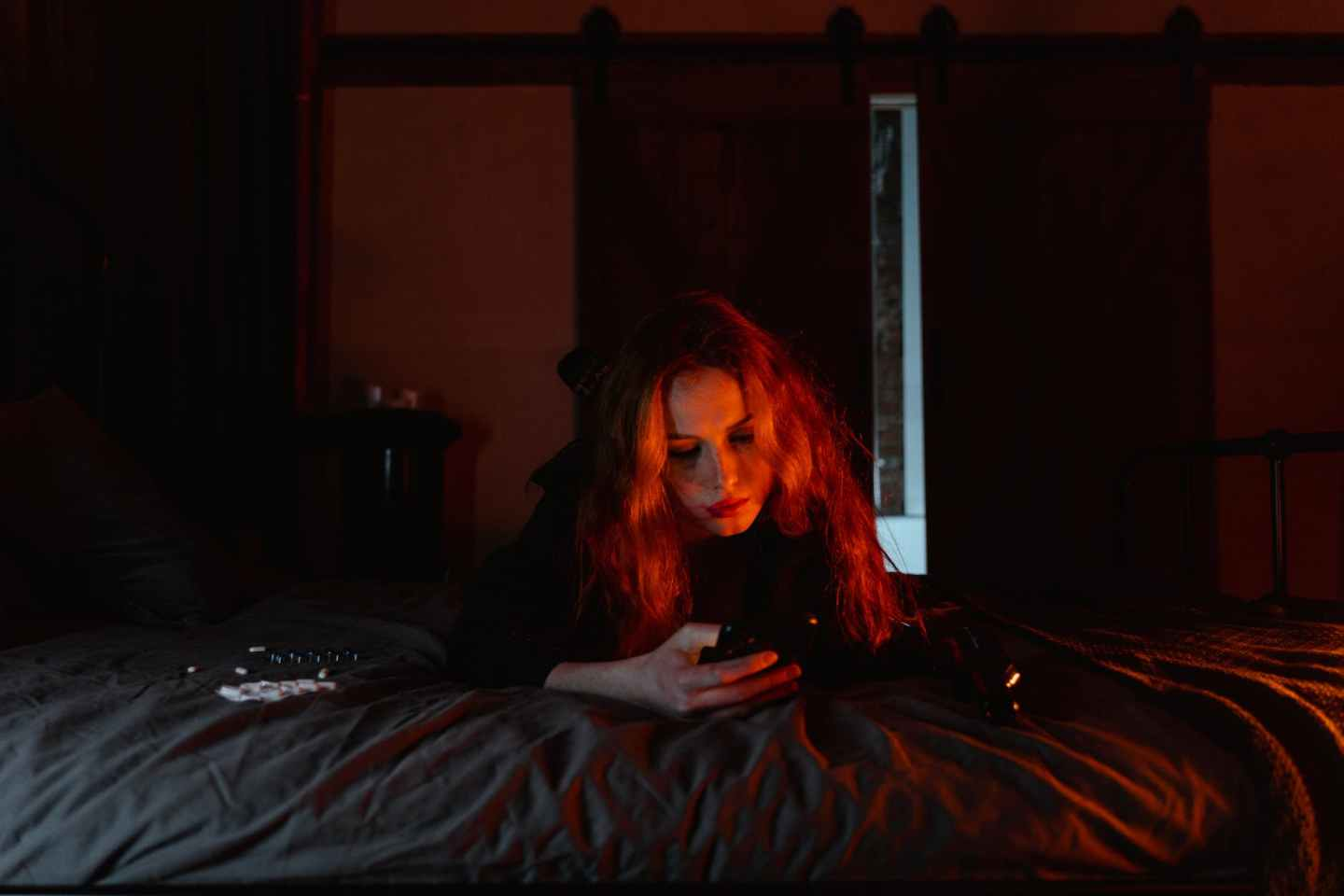 woman lying on bed with cellphone