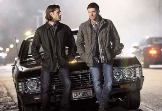 Sam and Dean lean against the Impala