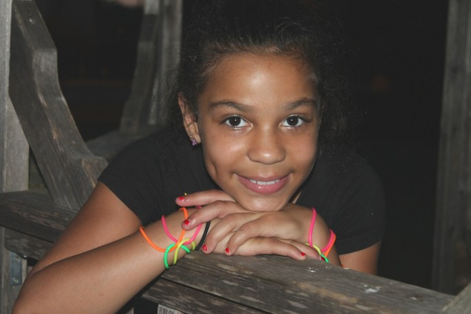 Young woman looks at camera with her head resting on her hands. She's wearing a black shirt and neon bracelets.