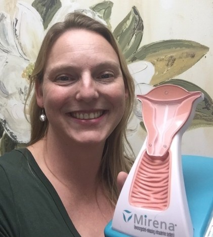 SciMom Anastasia Bodnar holding an anatomical model of a uterus and vagina with a Mirena IUD (intrauterine device) inside.
