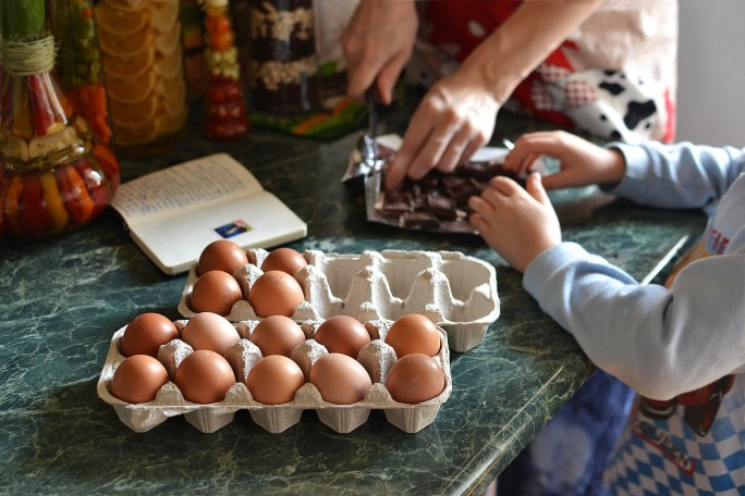 child and adult cooking eggs