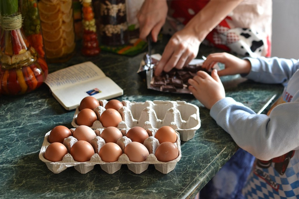 Eggs on a counter, with child and adult cooking. There are many food mantras about eggs.