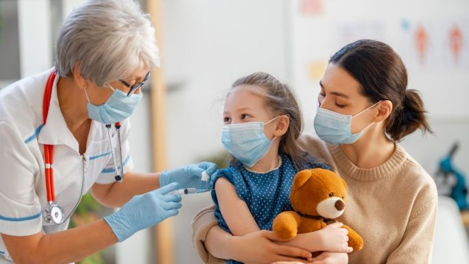child in mom's lab getting kids COVID vaccine
