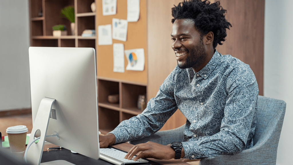 African American man looking at a computer and smiling