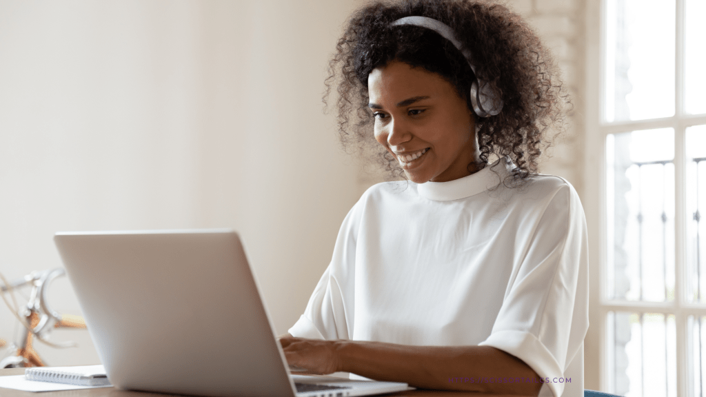 Young woman wearing headphones and smiling while using a laptop computer.