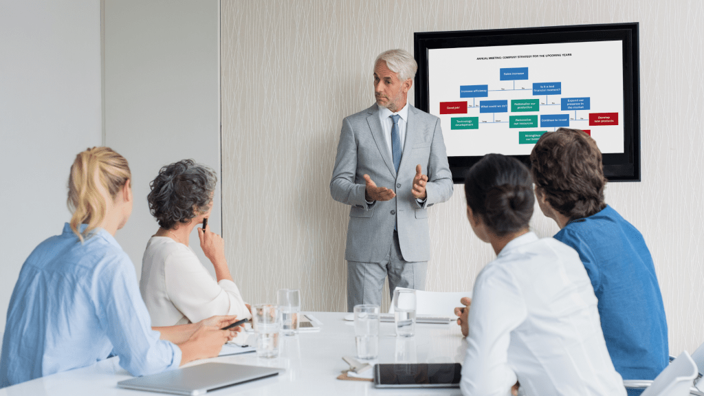 man giving a presentation with a slide displayed on a monitor