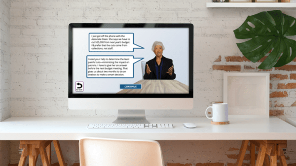 Computer on a desk, displaying a sample eLearning course with a Latina woman in her 50s sitting at a table speaking to the camera, with speech bubbles next to her. See long description.