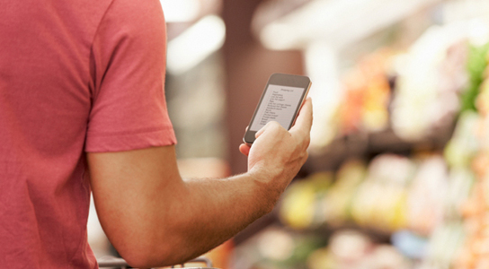 Close Up Of Man Reading Shopping List From Mobile Phone In Supermarket iStockphoto.com