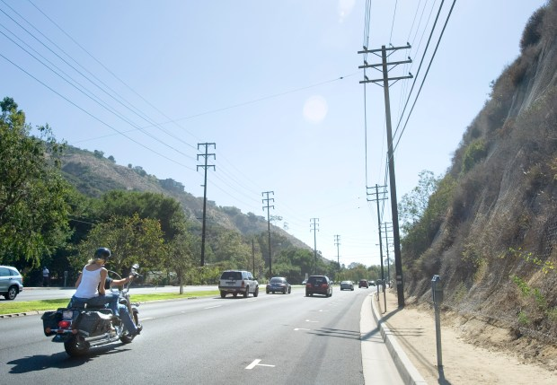 Motorists drive southbound along Laguna Canyon Road heading toward downtown Laguna Beach. Overhead power lines have long been a safety and aesthetic concern for Laguna Beach residents and officials. Downed power lines may have been a cause of the recent brush fire in South Laguna. (File Photo by H. Lorren Au Jr, Orange County Register/SCNG)