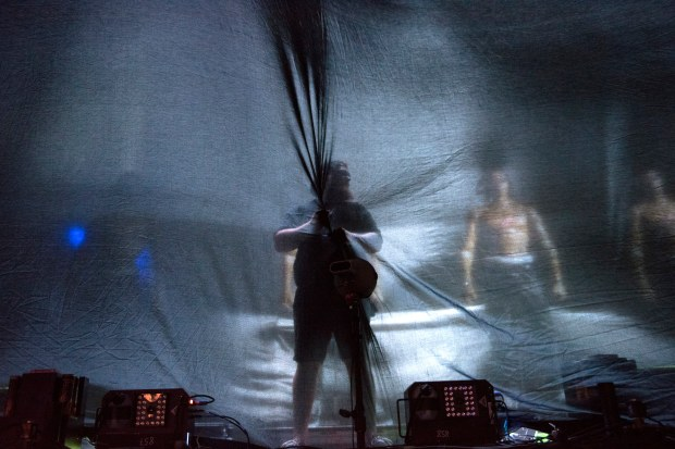 A stage hand tries to keep a curtain from blowing away before Travis Scott's set at Coachella Valley Music and Arts Festival in Indio on Friday, April 14, 2017. The wind won, the curtain descended a few moments early. (Photo by Matt Masin, Orange County Register, SCNG)