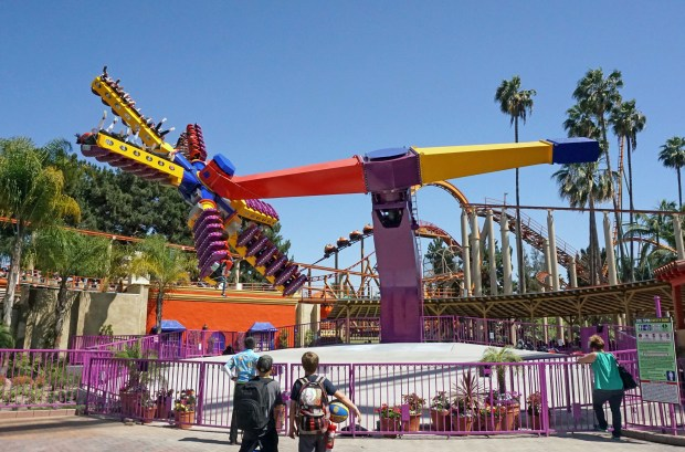 Visitors watch riders on the new Sol Spin ride at Knott's Berry Farm. The thrill ride holds up to 36 riders at a time, six on each arm. It spins around, goes up in the air, and turns riders upside down. The ride is on the platform where the Windseeker once stood in the Fiesta Village area of the theme park. (Courtesy, Knott's Berry Farm)