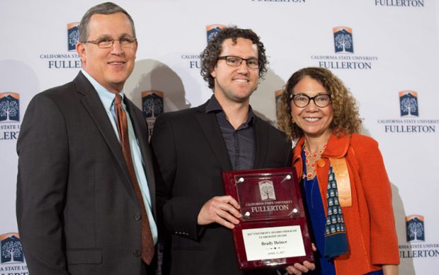 Cal State Fullerton assistant professor Brady Heiner is flanked by John Beisner, interim associate vice president for the Division of Human Resources, Diversity and Inclusion;  and Cal State Fullerton President Mildred García after accepting the Leadership Award at the University Awards Program. (Photo courtesy of Cal State Fullerton)