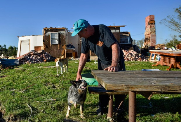 Edward Dougherty pets his dog Oakley outside of what is left of his home after a series of storms in the area, in Emory, east of Dallas, Texas, Monday, May 1, 2017. The outbreak that began Saturday over much of the U.S. Midwest and South included a series of tornadoes in east Texas and severe flooding after more than a foot of rain fell in parts of Missouri. (Chelsea Purgahn/Tyler Morning Telegraph via AP) ORG XMIT: TXTYL105