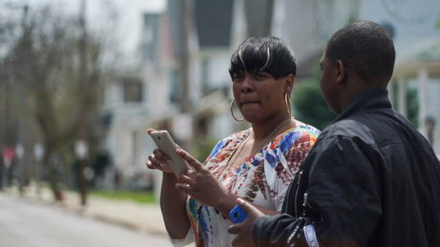 Alexis Lee, a childhood friend of Steve Stephens, speaks with a neighbor near Stephens' childhood home in Cleveland, Ohio, Monday, April 17, 2017. Authorities in Cleveland have expanded their manhunt nationwide for Stephens, a man suspected of gunning down a retiree and posting a video of the crime on Facebook. (AP Photo/Dake Kang) ORG XMIT: RPDK202