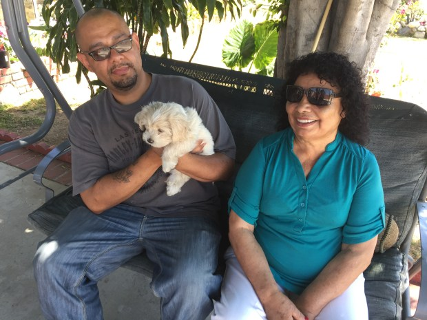 Erick Rodriguez sits next to his grandmother, Celia, holding Blanca. Blanca was rescued from a crash by a Riverside County Animal Services officer on April 4, 2017. (Photo courtesy of Riverside County Department of Animal Services)