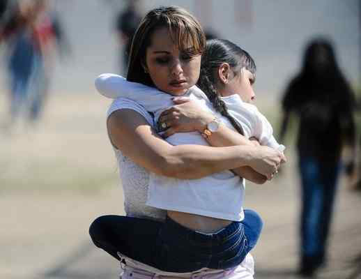A mother holds her daughter tightly as they walk off-campus after being reunited at Cajon High School in San Bernardino, Calif. on Monday, April 10, 2017. Two people and one child were killed, and another child wounded, in a shooting at North Park Elementary School in San Bernardino. (Photo by Rachel Luna, The Sun/SCNG)