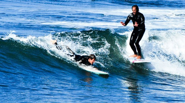 Newport surfer Tom Cozad tries to stop an inexperienced surfer from paddling into a wave he's already riding. File photo by Laylan Connelly