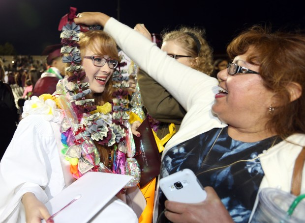 Rebecca Albano, left, has a lei placed on her by her aunt Charleen Williams, right, after West Valley High School's graduation ceremony Friday night at West Valley High School in Hemet, CA Friday, May 26, 2017. (Photo by Mark Dustin for the Press Enterprise/SCNG)
